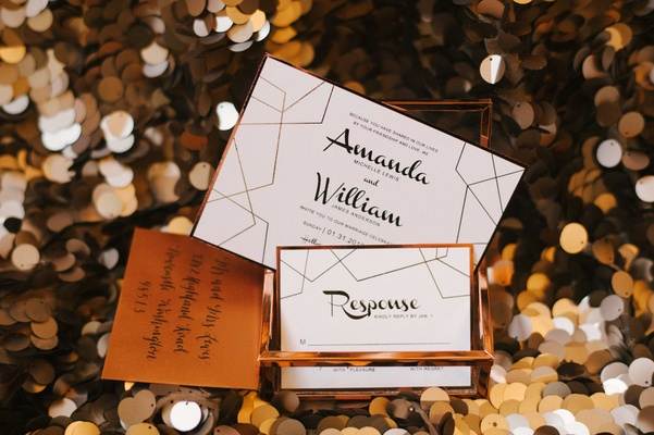 a contemporary style invitation with a white black and copper color scheme