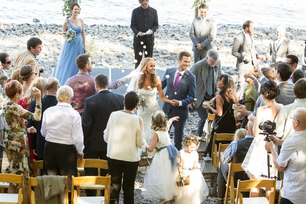 flower girls toss petals at bride in pronovias and groom during recessional