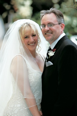 Bride in a veil and groom in a black tuxedo with a striped black-and-silver tie