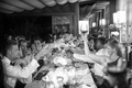 Black and white photo of guests toasting at a wedding reception dinner