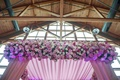 Exposed wood beams and purple ceremony altar