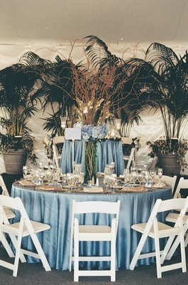 Indoor palm trees and blue wedding reception tables