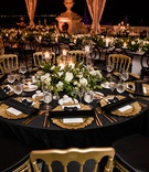 wedding reception table, gold chairs, black linens and napkins, gold charger plates, green and white