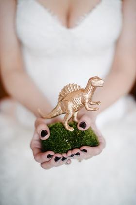 Bride holding moss pillow with golden dinosaur figurine