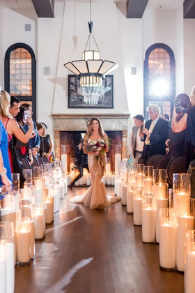 bride in blush inbal dror wedding dress fall bouquet candle lined aisle guests taking phone photos