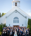 Bride and groom with bridesmaids, groomsmen, and friends and family in front of church after ceremon