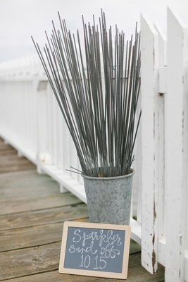 DIY chalkboard sign for sparkler send off with tall sparklers in tin next to white picket fence