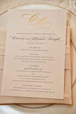 Wedding reception menu with couple's golden monogram on linen napkin, white china plate with gold