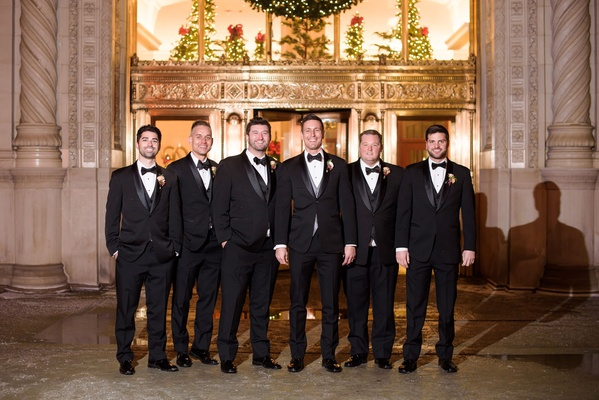Groom and groomsmen in three piece suit tuxedos bow ties in front of altar wedding ceremony church