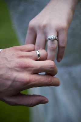 Hands of bride and groom with respective wedding rings