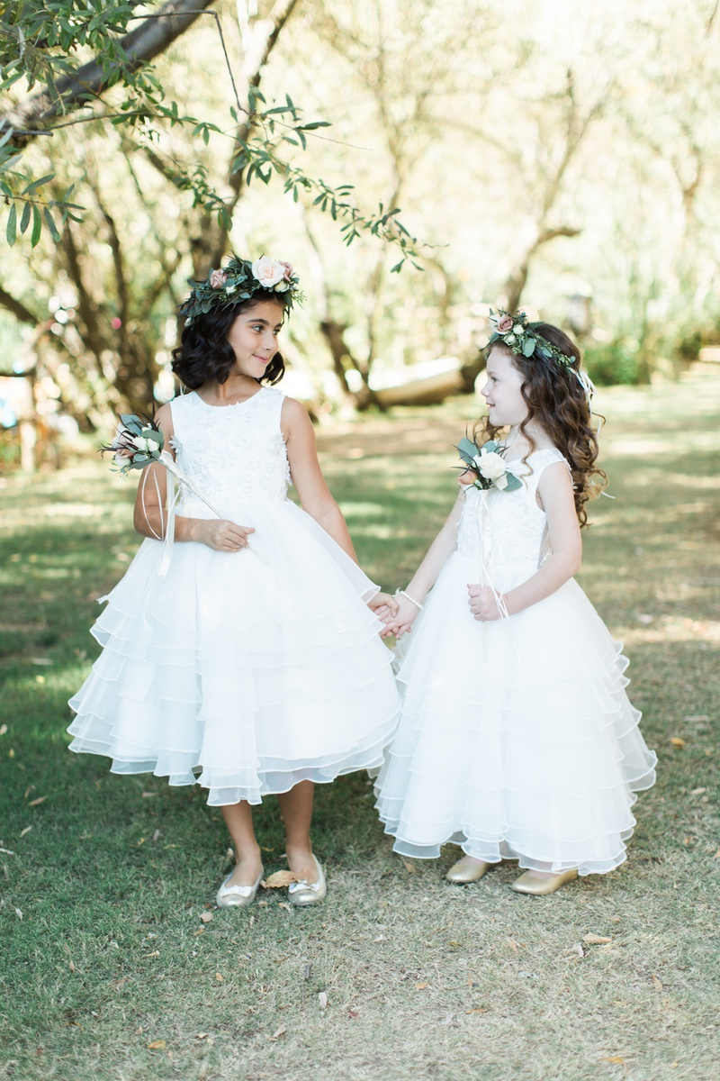 two flower girls with white dresses, flower crowns, flower wands
