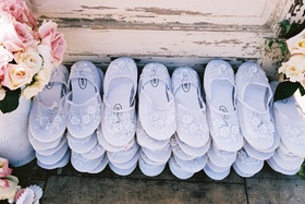 White slippers for guests to wear on sand at beach wedding