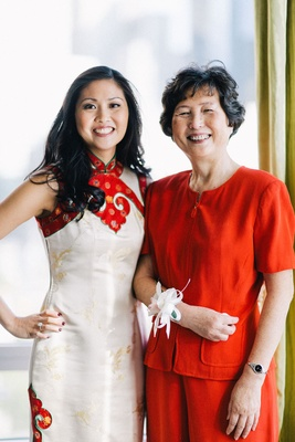 Bride in a white Qipao with gold embroidery, red trim with mother in a red outfit and white corsage