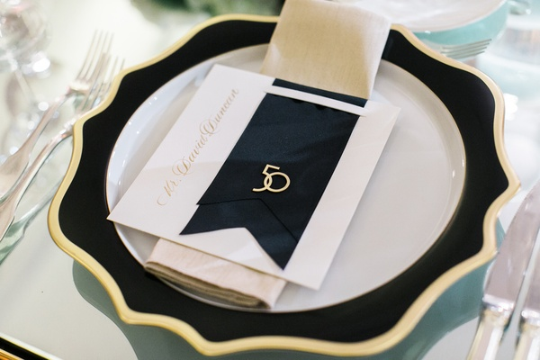 charger plate with wavy black and gold border, place card with black ribbon and gold 50