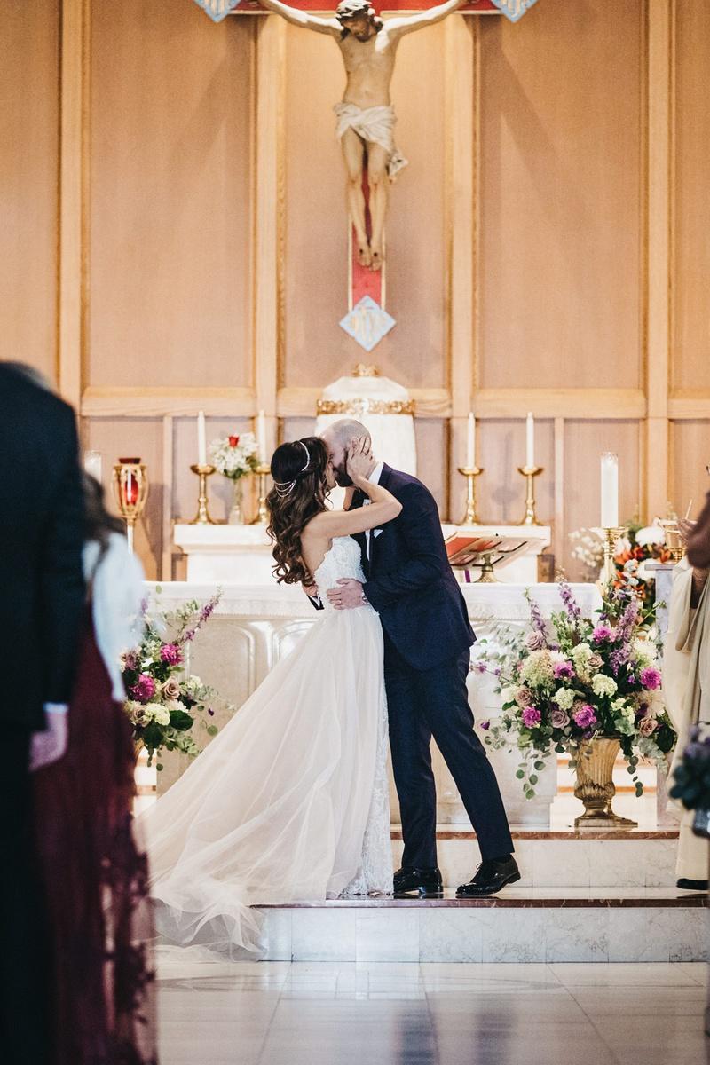 groom kisses bride during Roman Catholic church ceremony