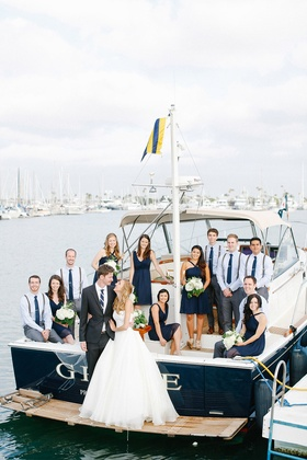 Bride and groom with nautical blue wedding party on family boat in bay in San Diego