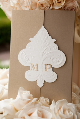 Wedding invite with monogram on fleur de lys fastener