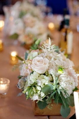 Wedding reception table with white hydrangeas, roses and greenery in a rustic wood box