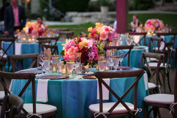 Wedding reception with wood chairs around table with turquoise tablecloth