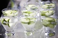 Glass cups with slices of cucumber floating on water