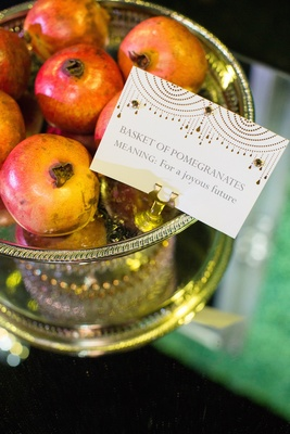 Silver bowl of pomegranate fruits at wedding sofreh table