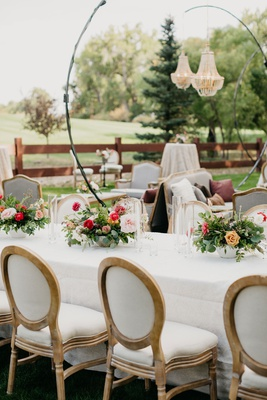 wedding reception stand up chandelier white table french upholster chairs pink centerpiece greenery
