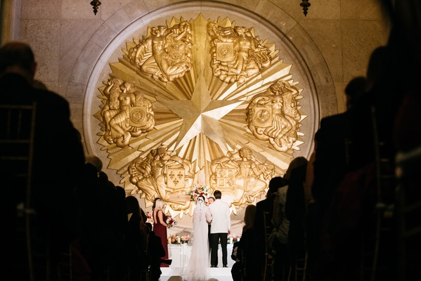 The Hall of State at Fair Park wedding ceremony gold star at altar decor minimal decorations