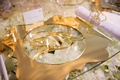 Glass table with flowers beneath glass gold charger plate die cut with monogram in center laser cut