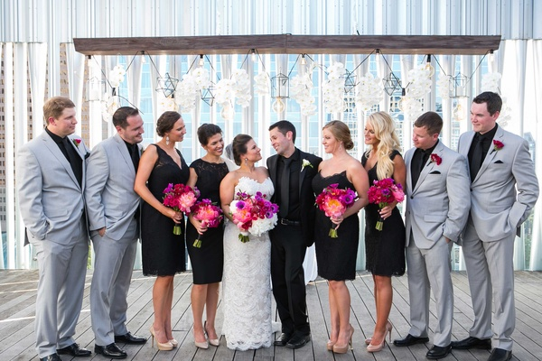 bridesmaids in black cocktail dresses and groomsmen in grey suits look in at newlywed couple