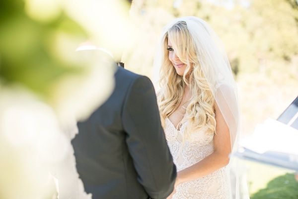 bride with veil galia lahav wedding dress long blonde hair curls looking at groom during ceremony