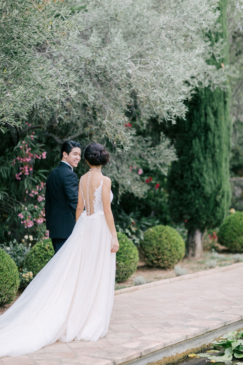 bride with illusion back wedding dress with tulle skirt and train, walks down path with groom in tux