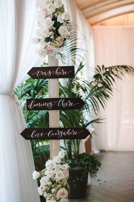 Wood sign with white calligraphy flowers on top and base of post for wedding