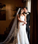 cathedral-length veil, sweetheart neckline gown portrait of bride and groom by window