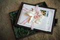 brown and white invitations tied with pink ribbon and white flower