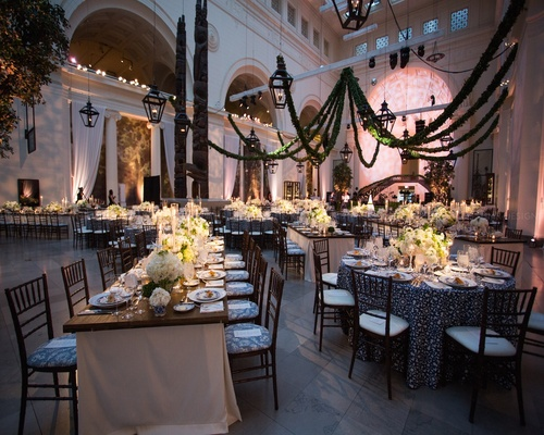 Room view with ivory centerpieces and greenery abounding.