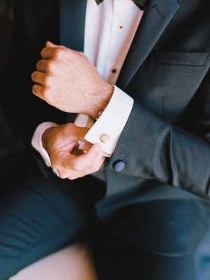 Groom in tuxedo with bow tie putting on cufflinks cuff links round gold