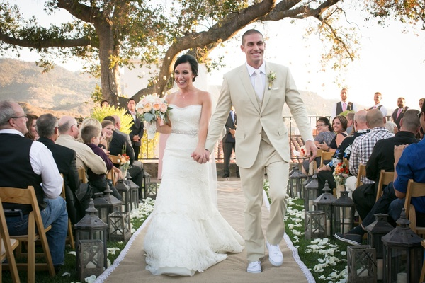 Bride and groom walk down lace and burlap aisle runner