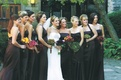 Bridesmaids in long mismatched dresses carrying bouquets in different fall colors