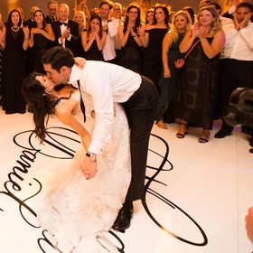 Wedding reception bride and groom dip and kiss during first dance on personalized dance floor names