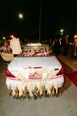 Wedding getaway car white Mercedes SL550 with just married letter sign and gold tassels streamers
