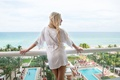 bride with long blonde hair in white personalized robe overlooking pool at acqualina resort and spa