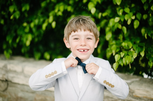 ring bearer in light suit and navy bow tie