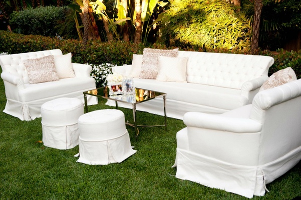 White sofa and settee on grass lawn at wedding ceremony