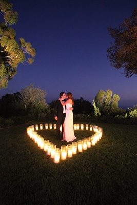 Katherine Kallinis and groom kiss inside heart made of candles