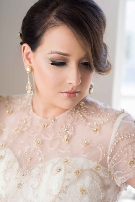 Bride with beautiful makeup and updo with diamond earrings and ball gown with gold flower details