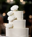 wedding cake classic white three tier with fresh white rose on top and layers classic design
