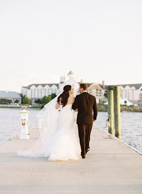 Bride and groom walking on plank in wedding attire