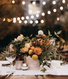 outdoor wedding reception bistro lights small centerpiece kumquats fresh fruit orange dahlia greens