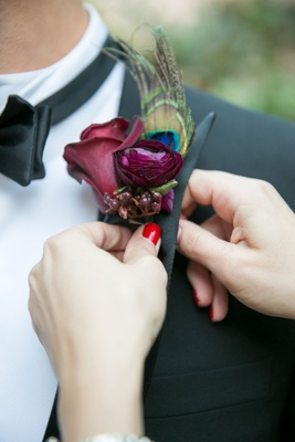 Woman with red nail polish putting on boutonniere lapel for groom peacock feather and purple flowers