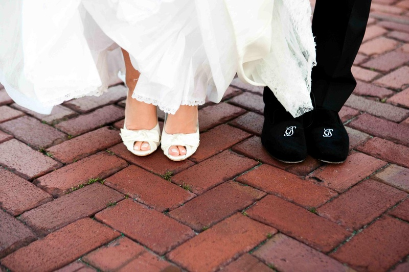 Bride in peep-toe pumps and groom in monogram shoes